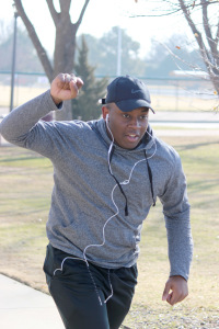 Keith Ngondo, nursing freshman, crosses the finish line first with his fist up at the one mile Cookie Dash set by the University Programming Board at Sikes Lake, Jan. 23, 2016. Photo by Francisco Martinez