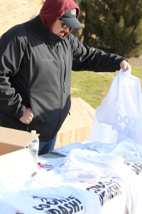 Mario Ramirez, activities coordinator student development and orientation, sets up the t-shirt table during the 1 mile Cookie Dash put on by the University Programming Board at Sikes Lake, Jan, 23. Photo by Francisco Martinez