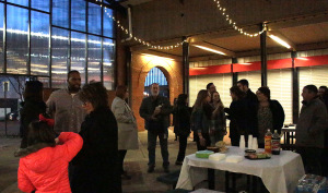 Group of attends conversing at the Graphic Design Pop-up Exhibit at the Wichita Falls Downtown Farmer's Market on Jan. 26th. Photo by Kayla White.