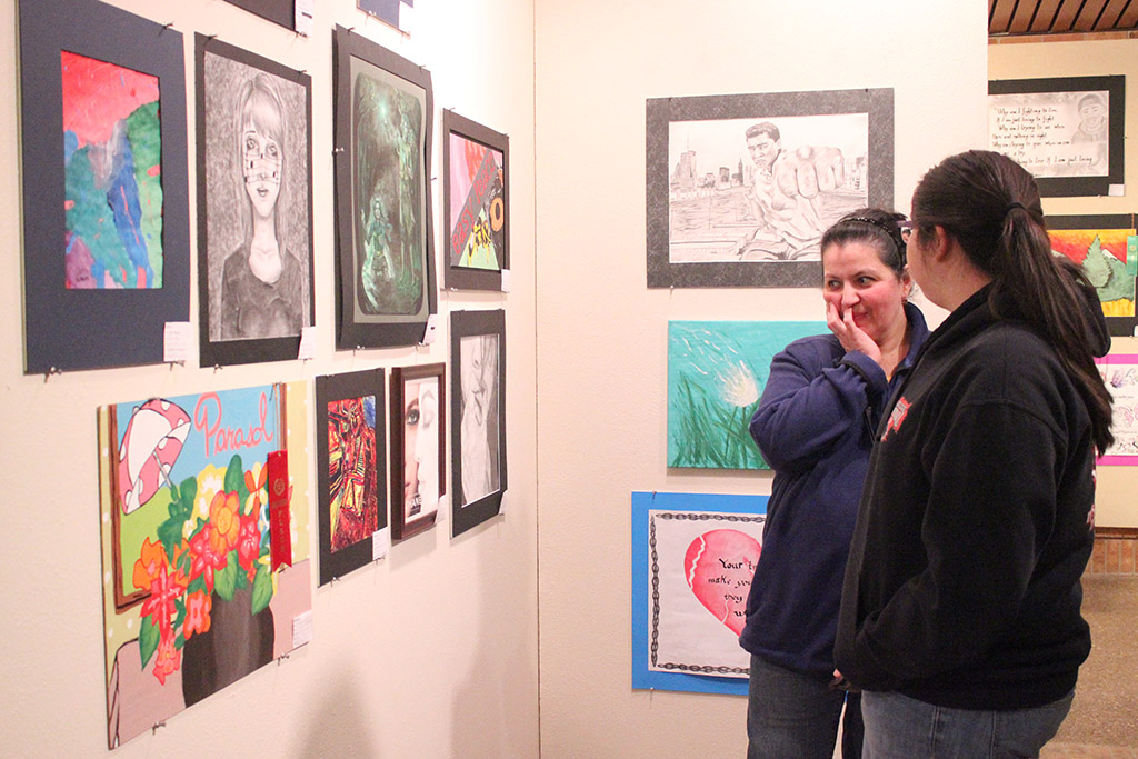 "Jasmine Barron, Old High student and contestant, looks at art work with her mother, Graciela Barron, during The Juanita Harvey Art Gallery: Opening Reception for High School Art Competition held on Feb. 6 in Fain Fine Arts. ""I just really like [doing art] as a hobby. It makes me relaxed and all my emotions and frustrations onto that piece,"" Barron said. Photo by Rachel Johnson"