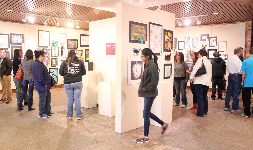 High school students, professors, teachers, parents, and gather around the High School student's art displays for the The Juanita Harvey Art Gallery: Opening Reception for High School Art Competition Feb. 6. Photo by Rachel Johnson
