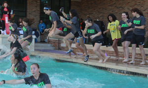 """The Coyote Softball Team plunges on Jan. 30. Wichita Falls High School held a competition between teachers and whichever teacher had the most money put in their bucket had to jump. Coach Bingham """"won"""" and the team decided to jump with their coach because they thought it would be a good bonding experience. Photo by Gabriella Solis"""