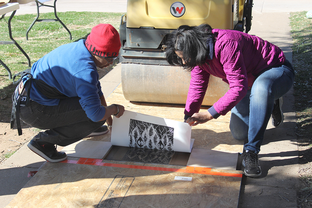 Lizca Bass, painting senior, and Auria Sanchez, teaching certification senior, unpeel the paper from the wood block to reveal the image for the Steamroller Print Event on Nocona Trial set up as a collaboration between MSU's Harvey School of Visual Arts and Wichita Falls Independent School District high schools, Feb 9, 2016. Photo by Francisco Martinez