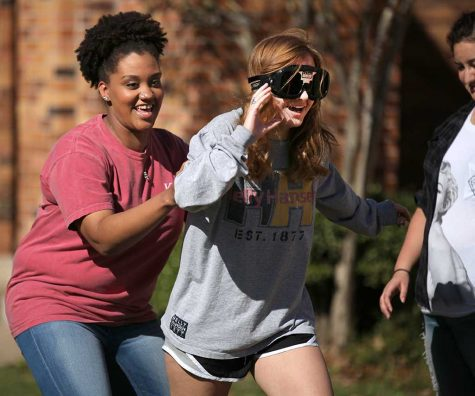 Tia Joyner, geology sophomore, spins Nicole Longely, education freshmen, as Longely prepares to run in the Drunk Goggle Relay finals on March 15. Photo By Dewey Cooper