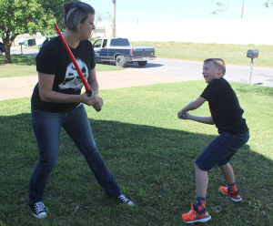 Jacklyn York, mass communication junior, and her son Braiden York play a game of light saber battle in the front lawn. Photo by Rachel Johnson