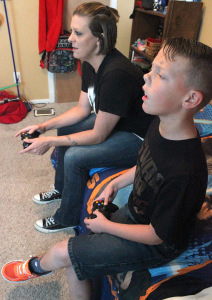 acklyn York, mass communication junior, and her son Braiden York play their favorite video game together in Braiden's room. Photo by Rachel Johnson