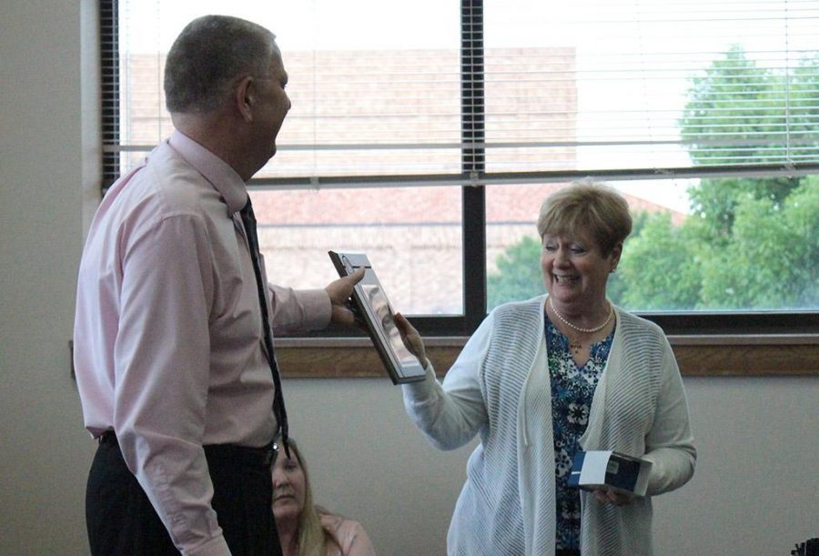 Dr. Hollabaugh reading his plaque given to her by Prof. Oxford on behalf of the university at the retirement reception for Dr. Hoffman & Dr. Hollabaugh in the 2nd floor atrium of Prothro-Yeager Hall on April 18. Photo by Kayla White.