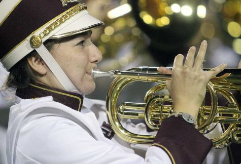 Rianne Busby, history junior, performs with the colorguard and marching band at the half-time show at Memorial Stadium, Sept. 26.