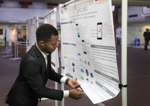 Enaho Atamenwan, mechanical engineering junior, sets up his poster on the MSU Smart Parking System. Photo by Topher McGehee