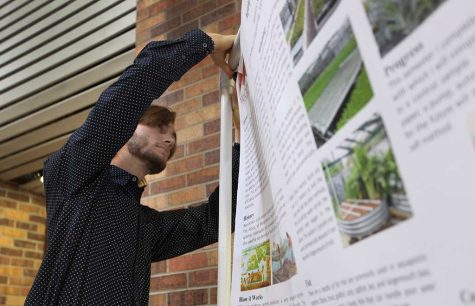 William Statham, mechanical enginering senior, adjusts his poster on aquaponics April 28. Photo by. Topher G. McGehee