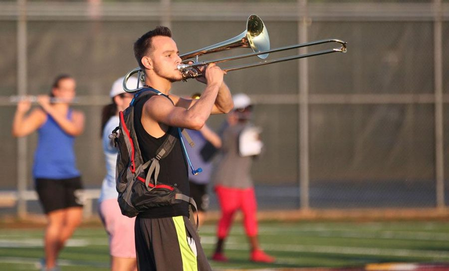 Adam McGee, music sophmore, practices trumbone on the field during band practice Aug. 24, 2016. Photo by Justin Marquart.