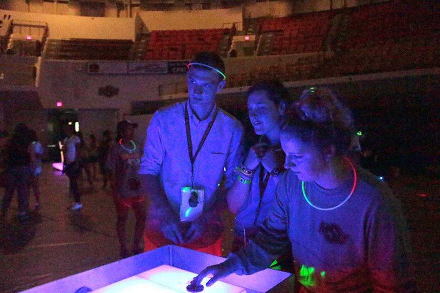 James Smith, mechanical engineering freshman, with Rachel Roberts, dental hygiene freshman, and Kaily Ashton, social work freshman playing shuffleboard at the Glow-cade in the D.L. Ligon Coliseum on Aug. 24. Photo by Kayla White.