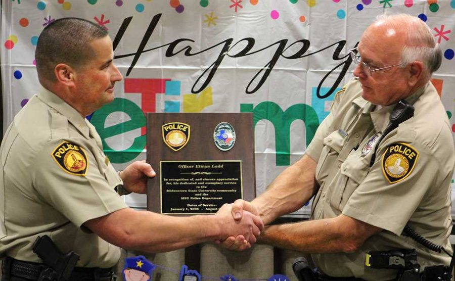 Chief Patrick Coggins presents Elwyn Ladd, police officer, with a plaque honoring his service with both MSU and the Wichita Falls Police Department. Photo by Jeanette Perry.