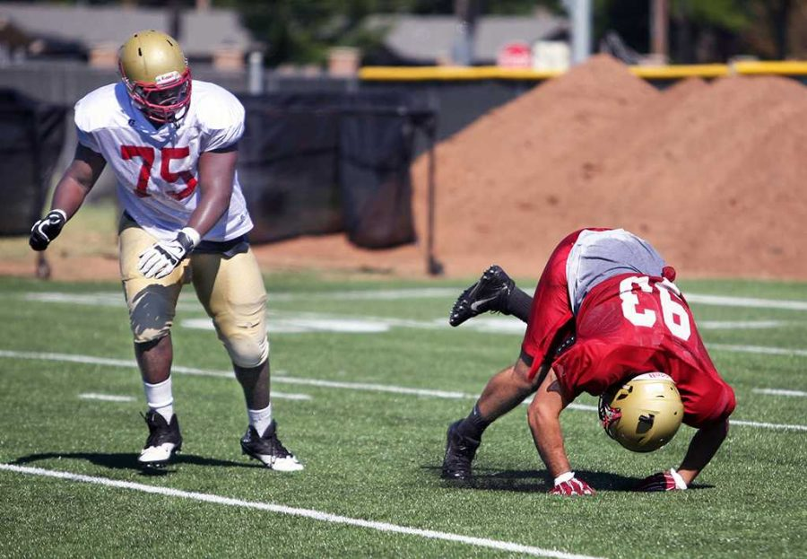 Joel Onyia, offensive line, watches as Darian Childers-Brown, defensive tackle, falls to the ground. Photo by Dewey Cooper.