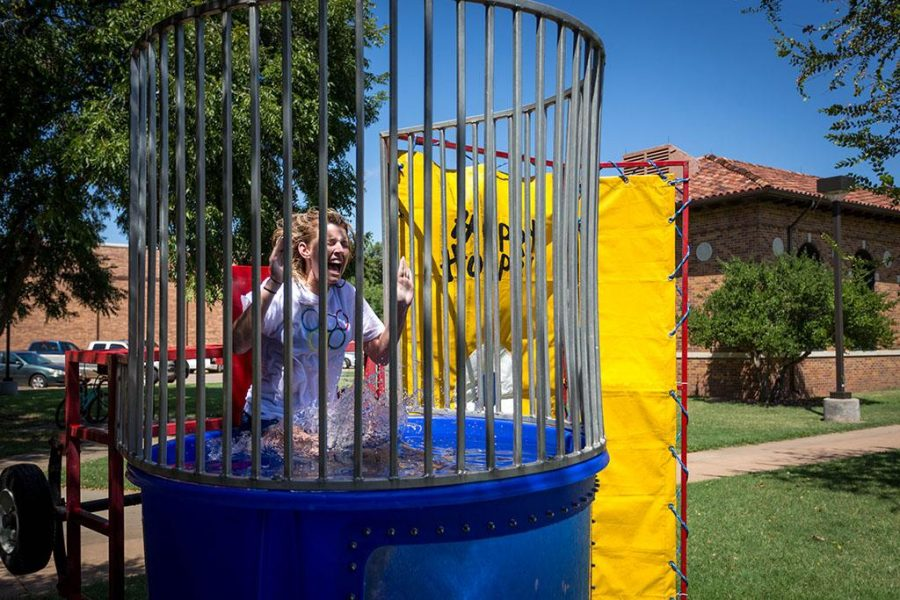 Morgan White, psychology sophomore, sits on the dunking booth during Roundup Olympics on the Quad Aug. 24. The water wasnt cold, she said. It feels uncomfortable being in the water in front of everybody. Photo by Izziel Latour