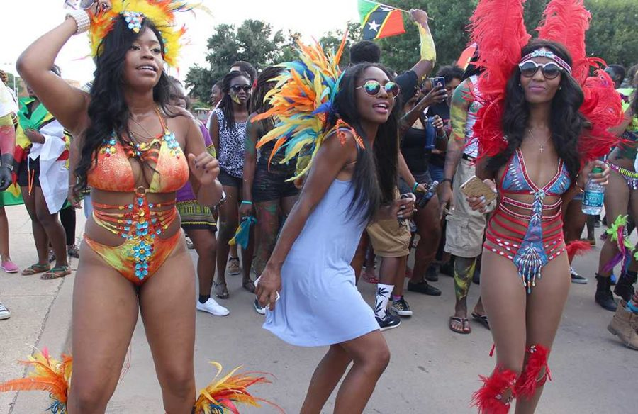 Nia White, political science junior, Barbara McGuire, criminal justice junior, and Kim Gundu, respiratory care junior, dance and sing behind a big truck blasting festive Caribbean music down Council Drive, turning onto Comanche Trail, Sept. 25, 2015. Photo by Rachel Johnson