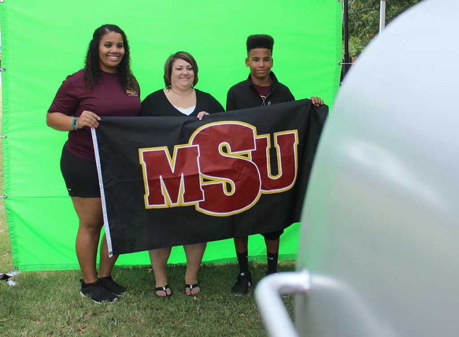 Sierra Jones, athletic training senior, Shana Hancock, mother of Sierra, and Devin Hancock, Sierra's brother, get their picture taken at one of the booths in the Quad put up for Family Day, Sept. 26, 2015. Photo by Rachel Johnson