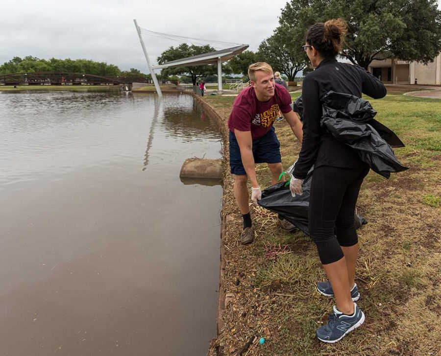 Brooks Rock, nursing senior, and Kassandra Alonso, nursing senior, help remove trash from Sikes Lake in 2016. Photo by Izziel Latour