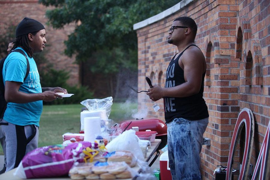Treston Lacy, mass communication junior, talks to Kyle Gordon, engineer senior, about Omega Delta Phi at the cookout held on the Sunwatcher Plaza on Sept. 13. Photo by Justin Marquart