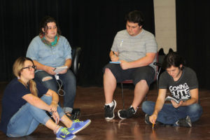 "Sarah Dempsey, theater sophomore, Hope Harwick, theater junior, Dean Hart, theater sophomore, and Joey McGrinn, theater sophomore, listen to notes during rehearsal for ""Speech and Debate,"" Sept. 15. Photo by Brendan Wynne"