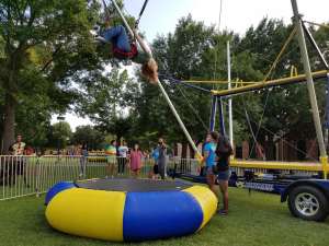 Elizabeth Corriere, athletic training freshman, flips on V5 Ultimate Bungee at UPB Block Party on Sept. 3, 2016. Photo by Caleb Martin.