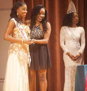 Kamilah Tobin, freshman in mass communication, accepts an award from Kinisha Morris, a junior in social work, in the Miss Carib Fest 2016. Photo by Naomi Skinner