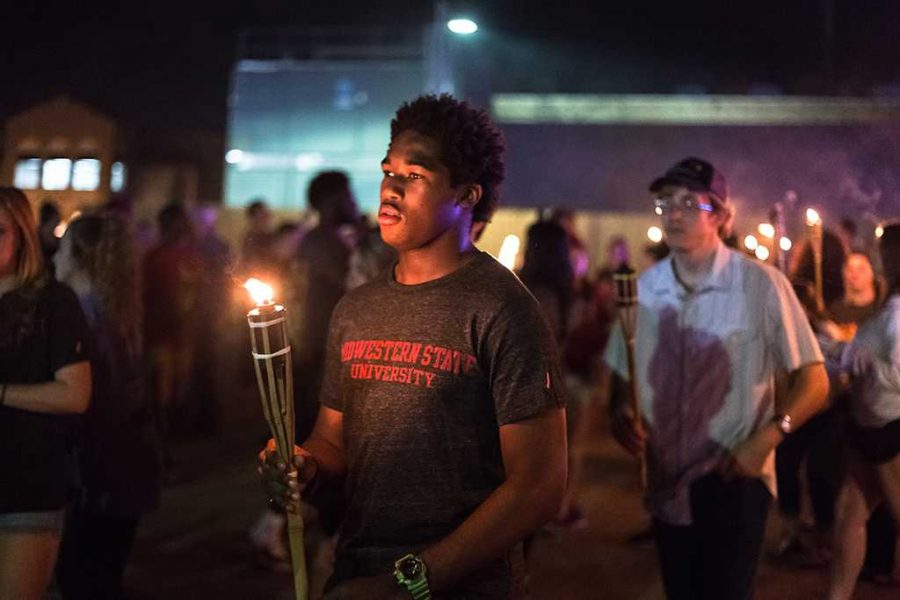 Christian Evans participates during the torch light parade on Oct. 27. Photo by Izziel Latour.