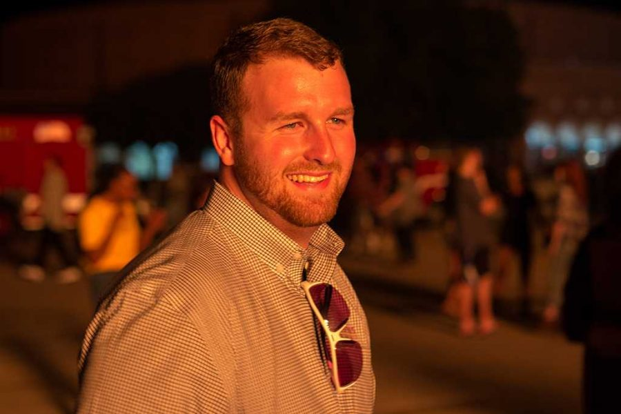 Jesse Brown, coordinator of student organizations and leadership programming, enjoys the warmth of the Homecoming bonfire on Oct. 27, 2016. Photo by Izziel Latour.