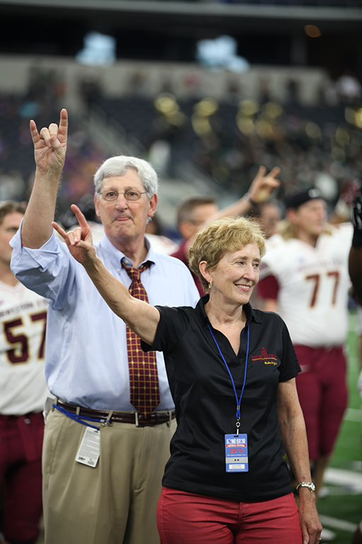 """Charlie Carr, athlectic director, and Suzanne Shipley, Midwestern State University president, throw up the """"stang sign"""" while the band prefoms the alma mater during the end of Eastern New Mexico University vs. MSU game at AT&T Stadium, Sept. 19. Photo by Francisco Martinez"""