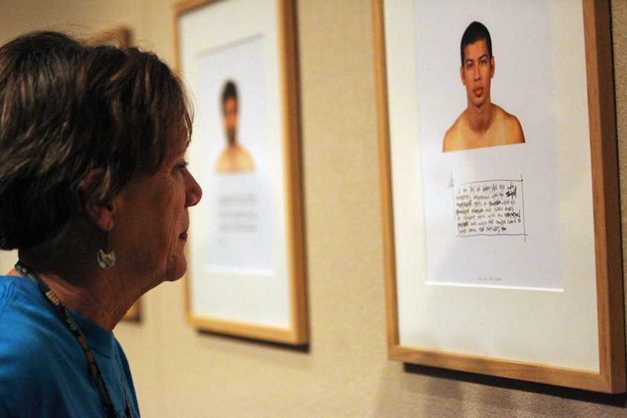 Emily LaBeff, sociology professor, reads one of Kip Fulbeck's Hapa Project gallery photos in the Juanita Harvey Art Gallery on Nov. 11. Photo by Bridget Reilly