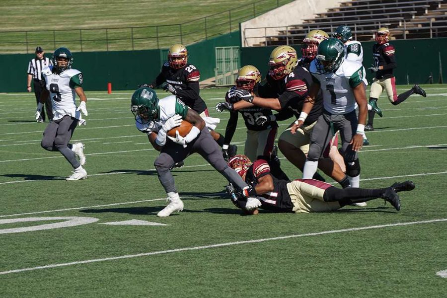 Marcus Wilkerson, mechanical engineering freshman, holds tightly to an Eastern New Mexico causing a group tackle on Sept. 12. Photo by Topher G. McGehee
