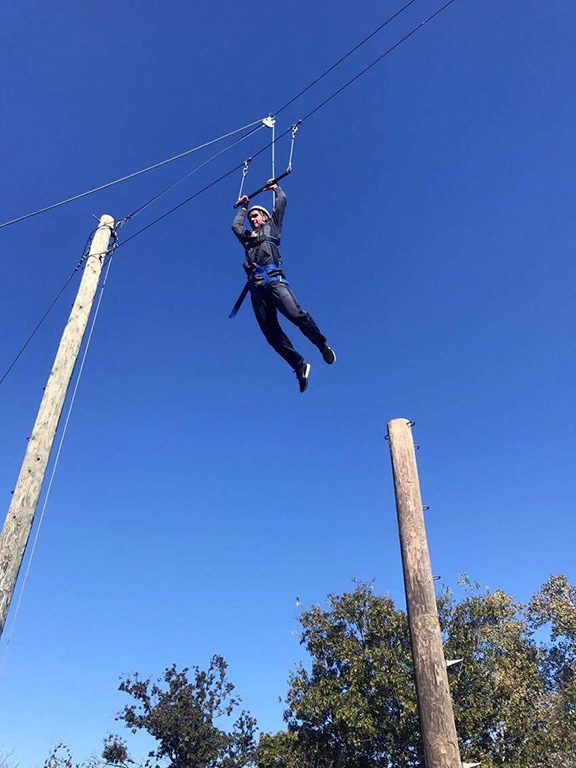 Management sophomore Greta Lazzarotto leaps for the bar during the ropes course. Photo by Zack Santagate