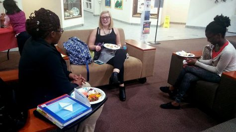 Psychology grad students Kietha Peters, Alyssa Morse, and Miriam Boateng enjoy their food at the International Potluck Monday night.