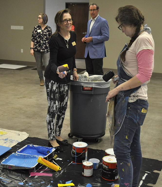 Mary Helen Maskill, public programs director at Wichita Falls Museum of Art, exchanges jokes over her mallet with Audra Lambert, local artist while she helps paint the background for the mural. Feb. 23. Photo by Arianna Davis