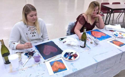 Natalie Griffin and Hannah Sommerhauser drink wine and paint hearts at the exploring arts acrylics class. Photo by Caleb Martin