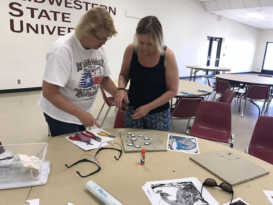 Cynthia Cummings, Clark Student Center special events coordinator, helps Lorraine Parmer, Continuing Education administrative assistant, score the glass for her project at the stained glass class on March 18 at the Sikes Lake Center. Photo by Sarah Graves