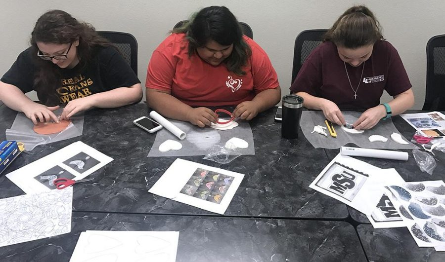 Bailey Hornsby, undecided freshman, Abigail Sanchez, radiology freshman, and Ariana Farris, undecided freshman, create their clay wind chimes on April 18 in the Caddo Room in the Clark Student Center. Photo by Sarah Graves