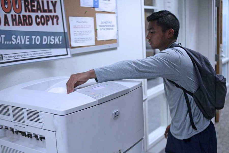 Dillon Pineda, exercise physiology sophomore, scans his ID card before getting his papers printed. Students use printing service of the computer lab in Clark Student Center. Photo by Timothy Jones