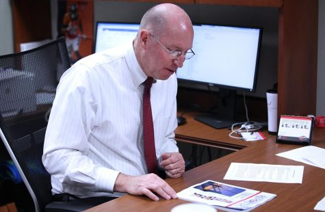 Jeff Stambaugh, associate professor of management and new dean of Dillard College of Business Administration, reads a magazine at his desk. Photo by Kara McIntyre
