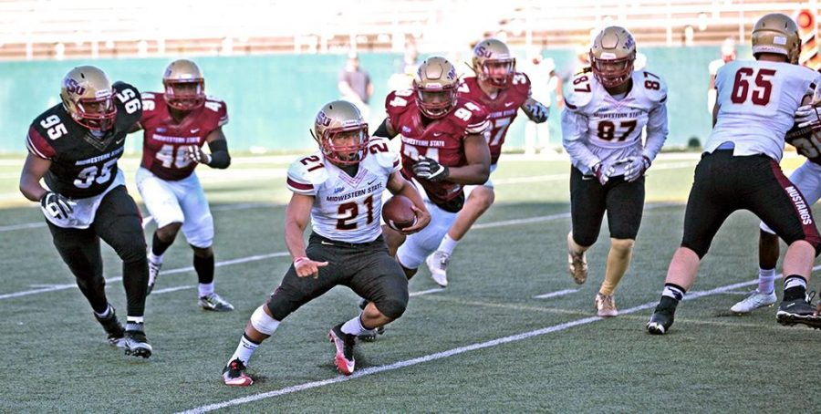 No. 21 S Steven Rogers, business management junior, jukes left on his way to a mutli-yard gain and a fresh set of downs.Gold were one touchdown better in a 9-2 win over the Maroon in the 29th Annual Spring Game, Memorial Stadium April 8.