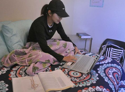 Audrey Beach, exercise physiology graduate, gets comfortable while studying on her apartment bed in Sundance Court. May 5. Photo by Arianna Davis