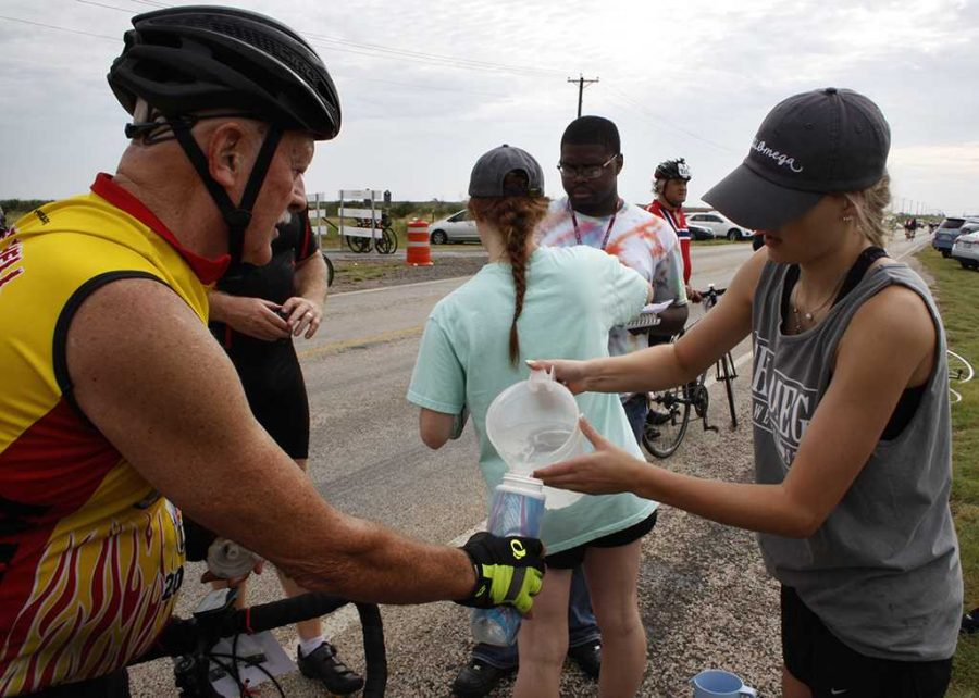 Gabi Woelffer, respiratory therapy junior, fills a cyclists water bottle at the Hotter 'N Hell 100 rest stop 5 in Burkburnett on Aug. 26. Photo by Justin Marquart.
