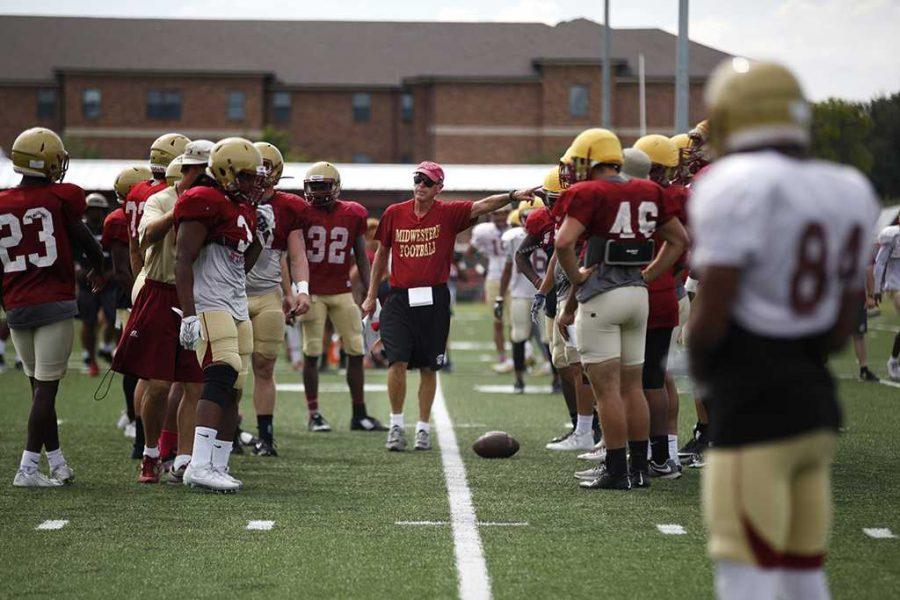 Head Football Coach Bill Maskill tells the football team how the play should be made during practice Aug. 27. Photo by Rachel Johnson