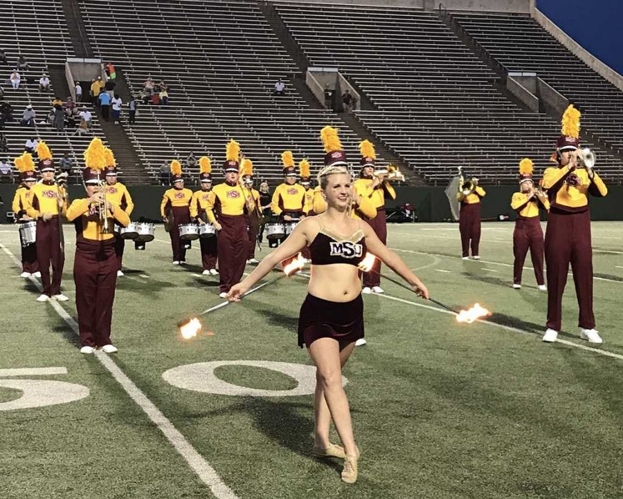 Alexis Maggard, special education freshman, twirls two batons on fire at the first home football game at Memorial Stadium on Aug. 31. Photo by Justin Marquart