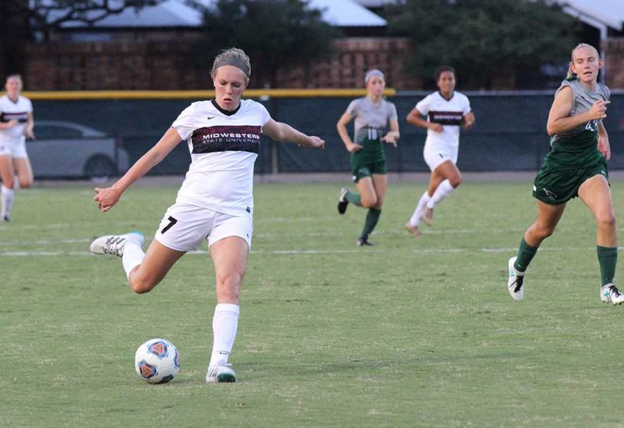Avery Lewis, undecided sophomore, passes the ball to her teammate to go for the goal during the game against Oklahoma Baptist, Sept. 15 which was held on Stang Park and the Mustangs won 3-2. Photo by Rachel Johnson
