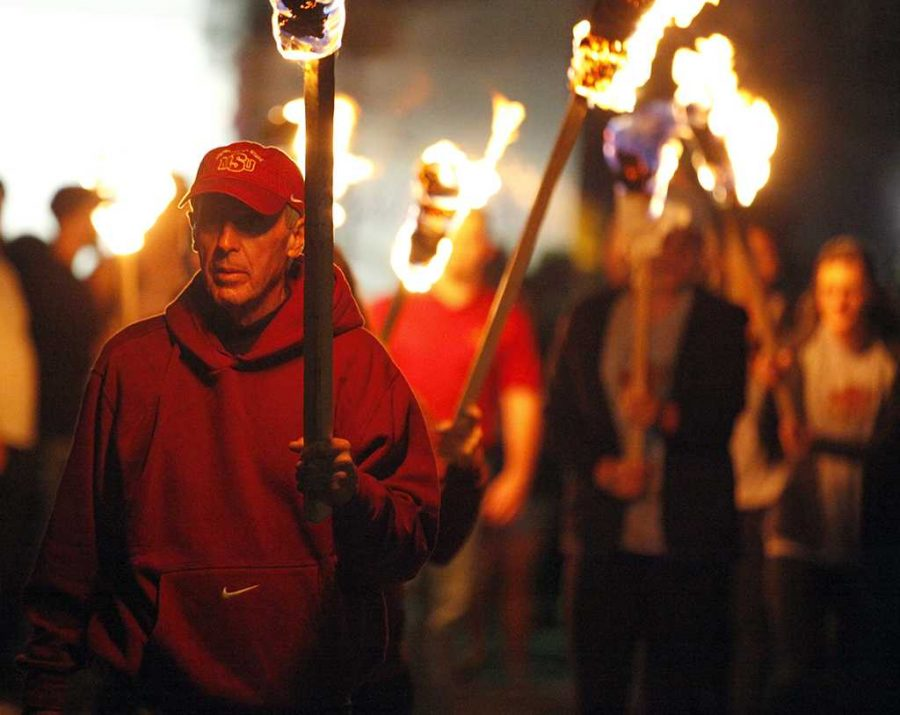 Bill Maskill, head football coach, walks through the crowd with a tiki torch to begin the homecoming bonfire, Thursday, Oct. 19, 2017. Photo by Francisco Martinez