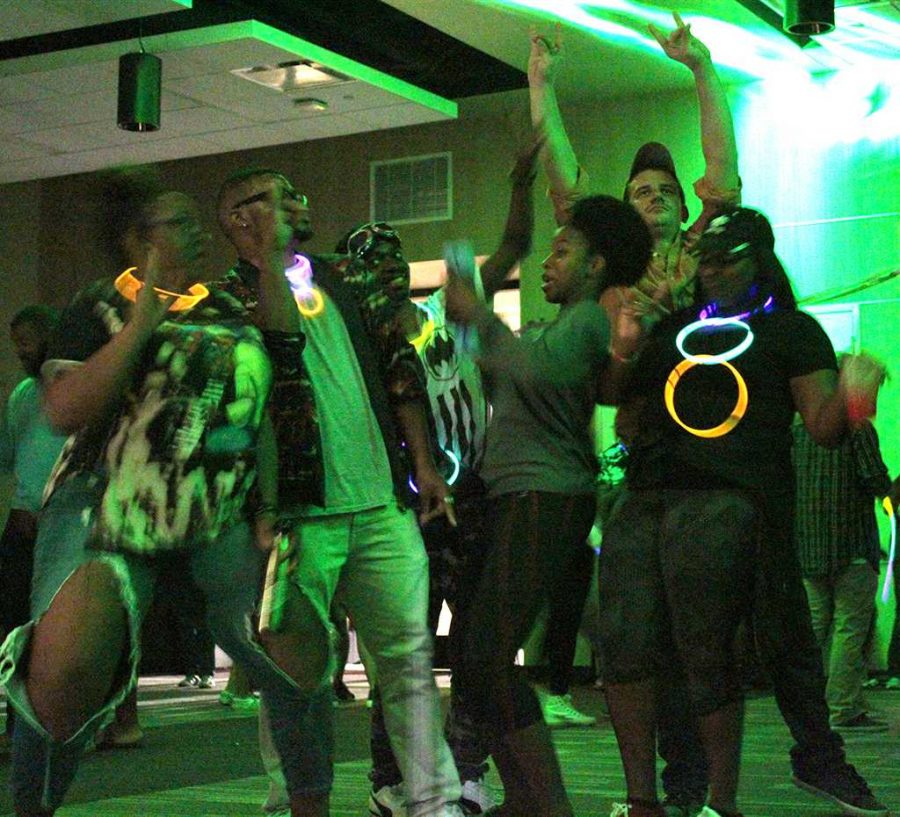 Participants in their 90's attire and glow sticks dance under the neon lights for the 2017 Homecoming Dance held in the Legacy multipurpose room on oct. 18. Photo by Marissa Daley