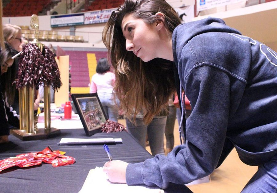 Amanda Bergstrom, incoming business marketing freshman, signs up for more information from the Midwestern State University Cheerleading Squad during the organization fair part of Mustangs Rally held in D.L. Ligon Coliseum, Saturday Oct. 28, 2017. I loved the large faculty here, and the faculty to student ratio [18:1]. I love how the professors really want to know you and how you are not just another number, Bergstrom said. Photo by Rachel Johnson