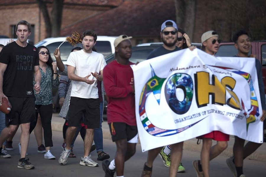 Luke Allen, 2017 spring graduate in political science, Maria Pena, political science senior, and Jacob Warren, economics junior, follow behind other students holding the sign for the Organization of Hispanic Students in the 2016 homecoming parade. Photo by Izziel Latour