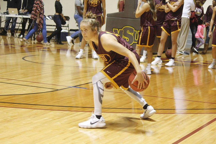 Liz Cathcart, marketing sophomore , practices her dribble and warms up for the game at mustang madness, Thursday, Oct 19, 2017. Photo by Sara Keeling